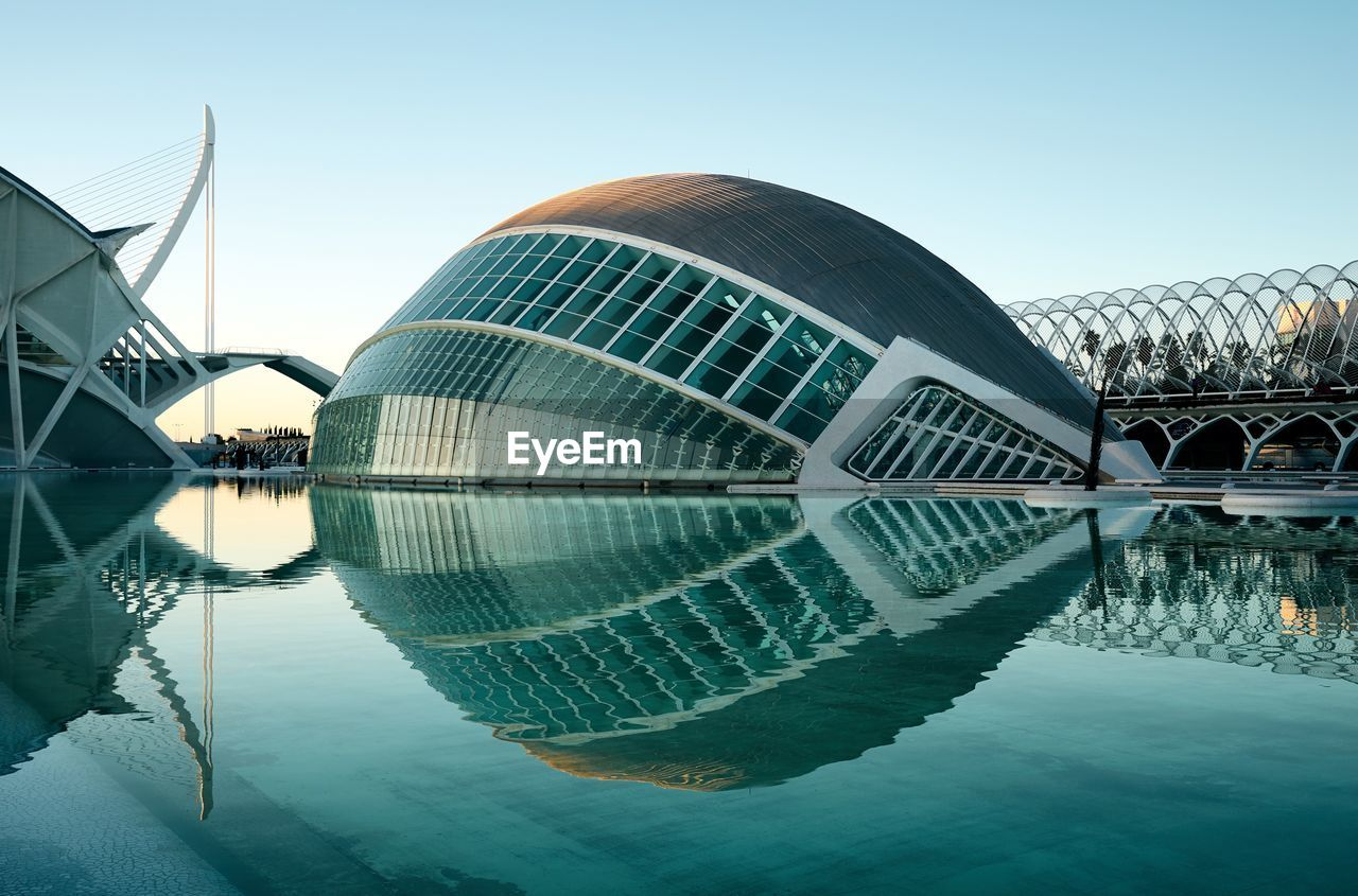 reflection, water, architecture, built structure, travel destinations, modern, reflecting pool, waterfront, building exterior, outdoors, clear sky, day, symmetry, city, sky, no people
