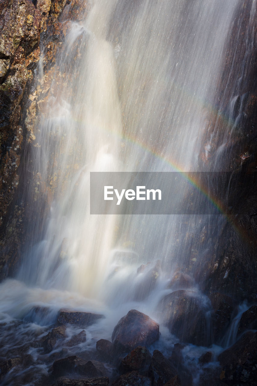 motion, water, long exposure, waterfall, scenics - nature, rainbow, blurred motion, rock, beauty in nature, flowing water, rock - object, solid, nature, flowing, no people, splashing, travel destinations, day, rock formation, outdoors, power in nature, falling water, spraying, purity, running water