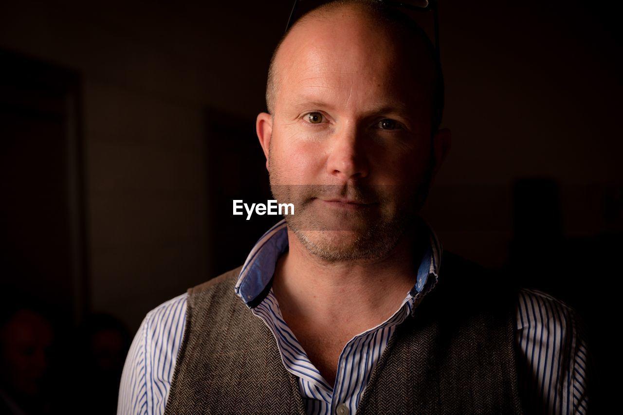 Close-up portrait of mature man standing in darkroom