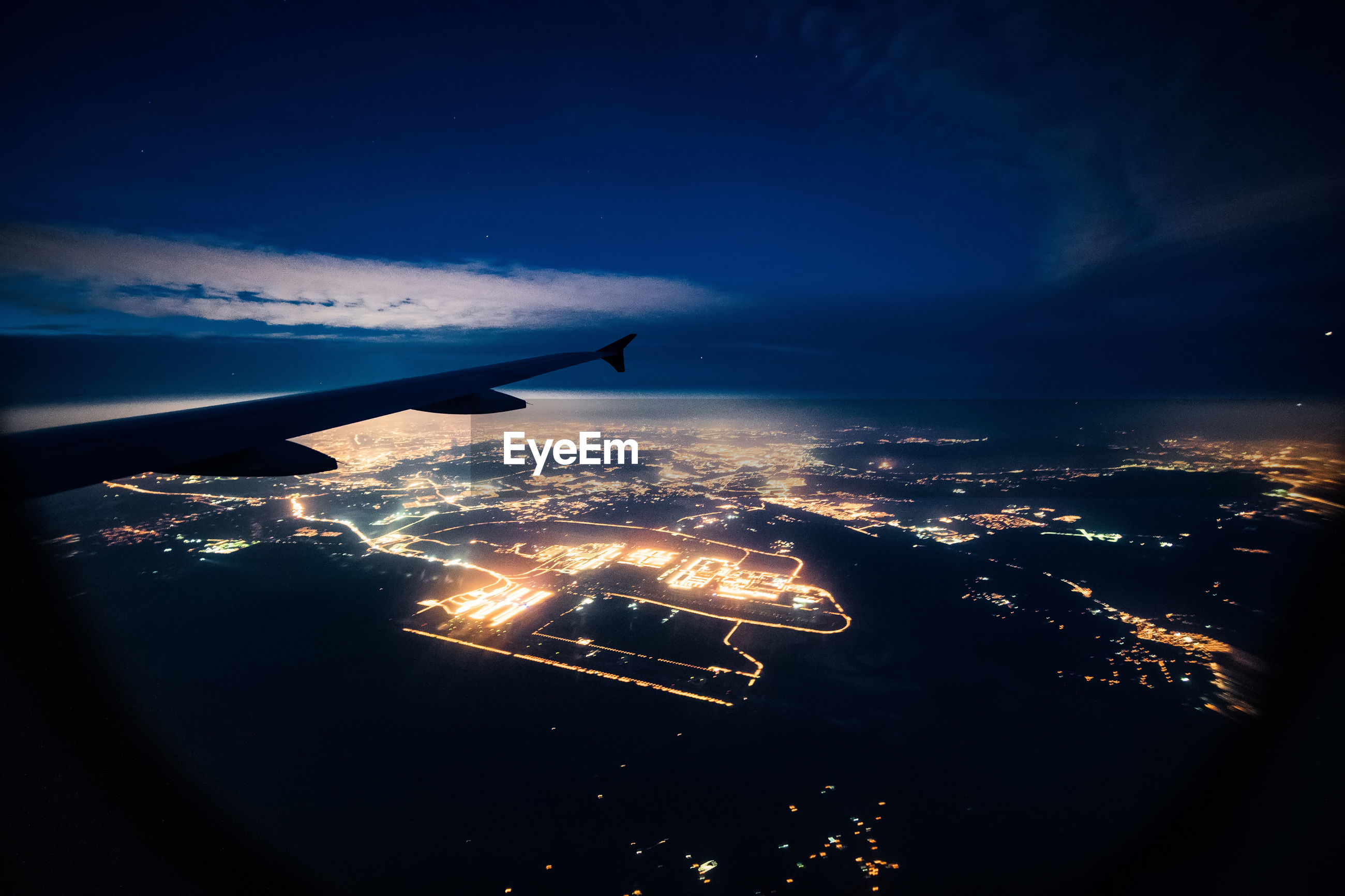 Aerial view of illuminated city against sky at night seen through airplane window