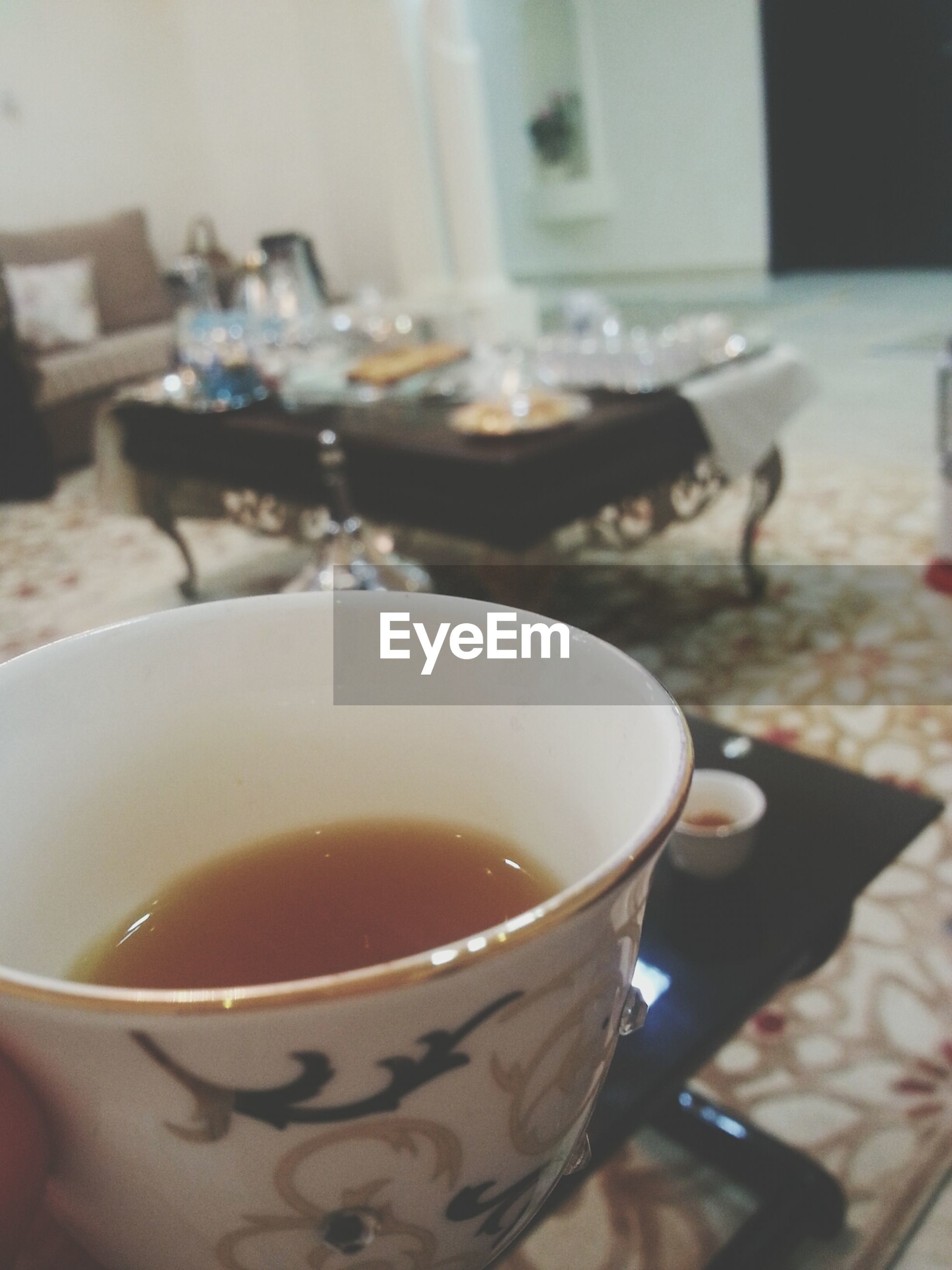 food and drink, drink, coffee cup, coffee - drink, refreshment, indoors, coffee, freshness, saucer, cup, table, frothy drink, cappuccino, close-up, focus on foreground, spoon, beverage, holding