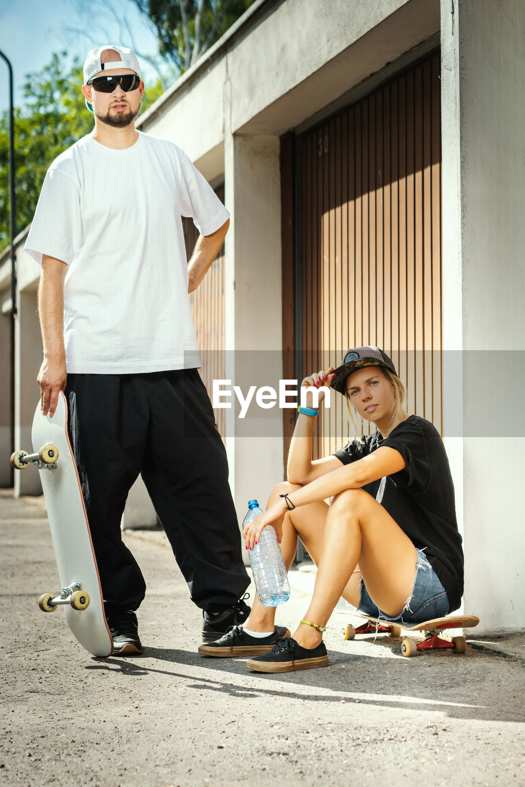 Portrait of couple with skateboards in city