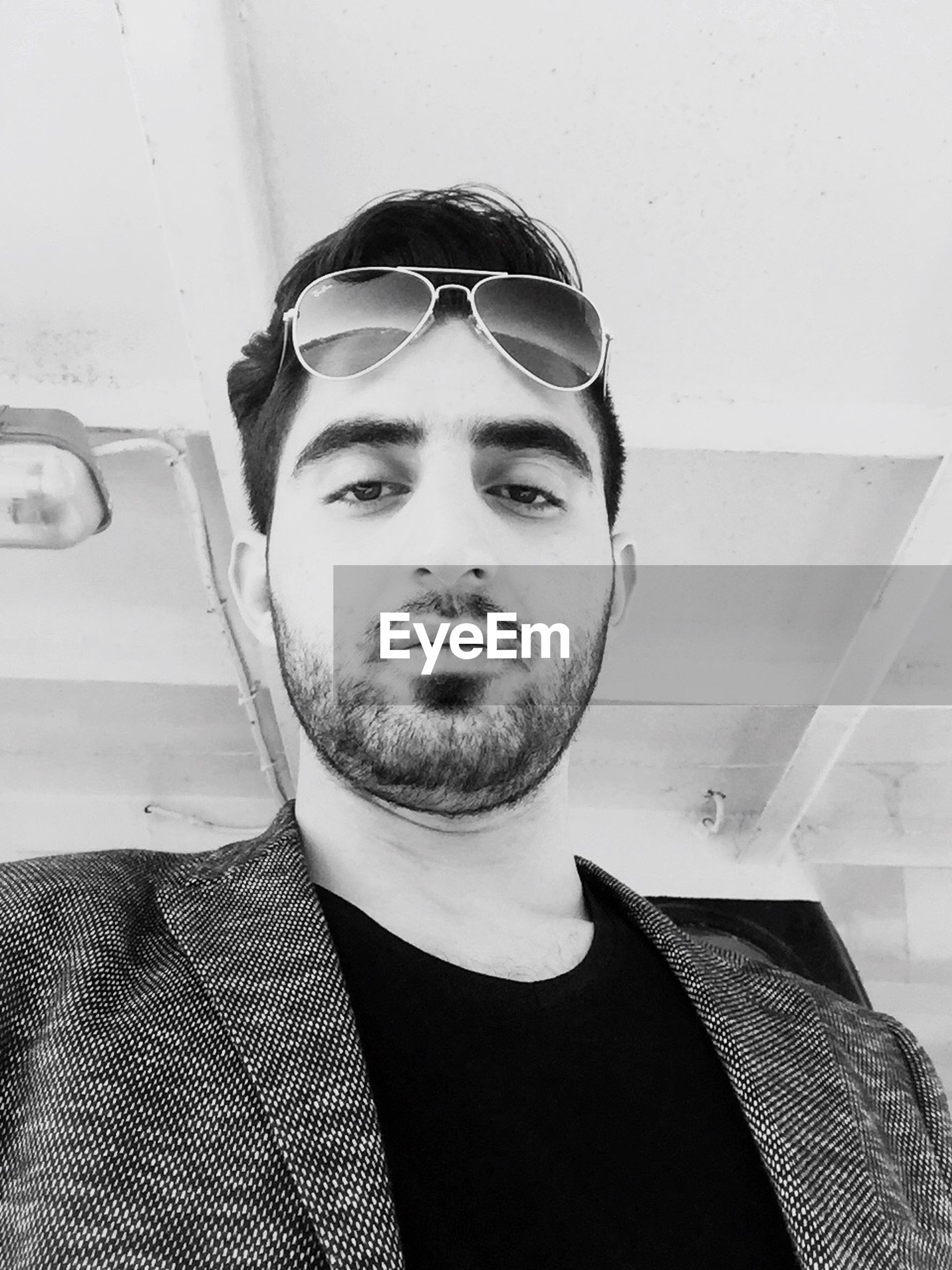 looking at camera, portrait, front view, lifestyles, young adult, person, sunglasses, young men, casual clothing, leisure activity, headshot, close-up, confidence, handsome, indoors, head and shoulders, day, smiling