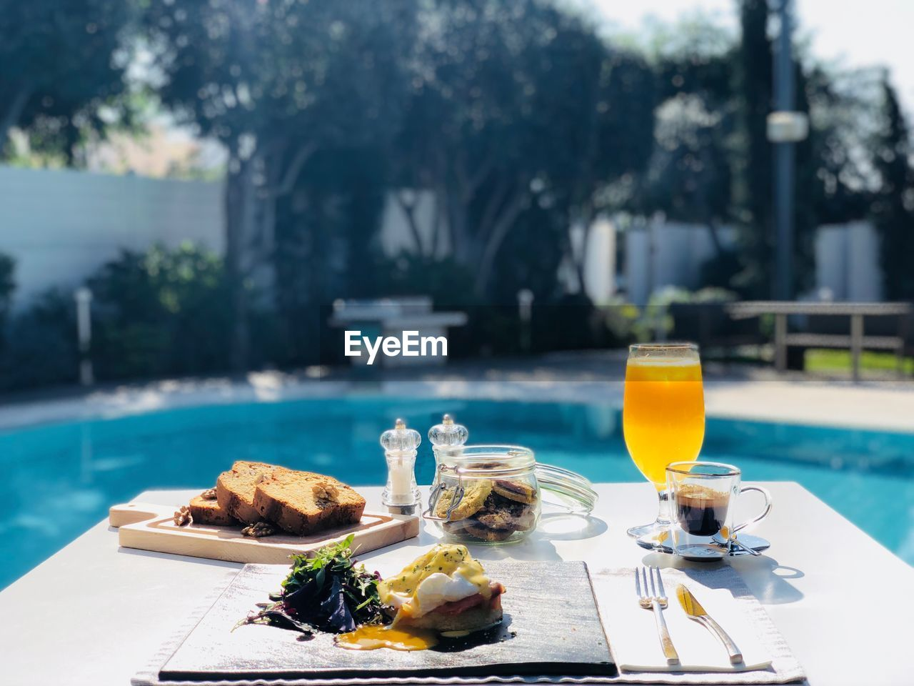 Breakfast served on table against swimming pool