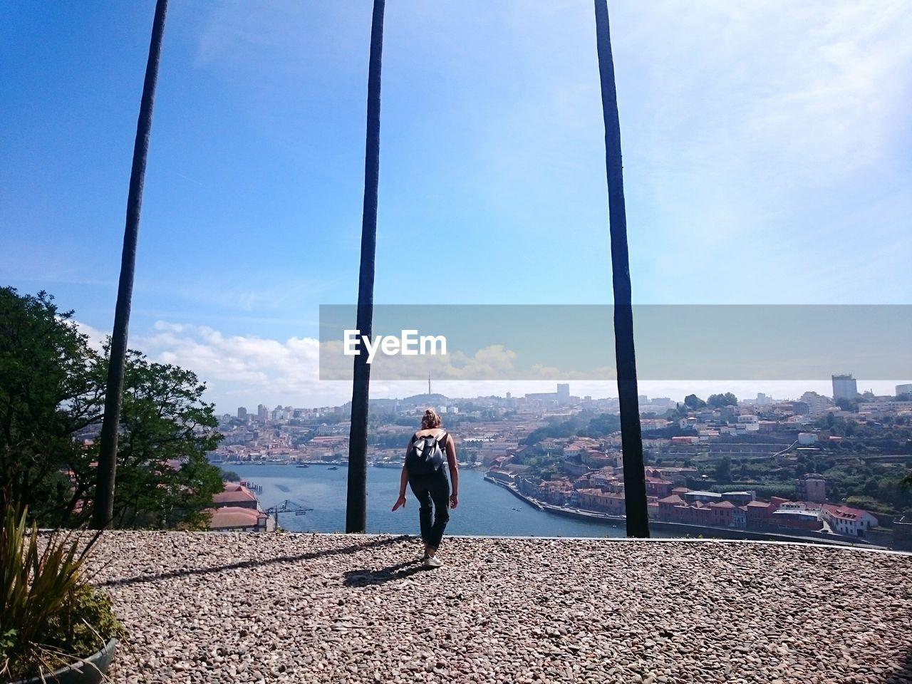 Rear View Of Woman By Poles At Jardins Do Palacio De Cristal Against Cityscape