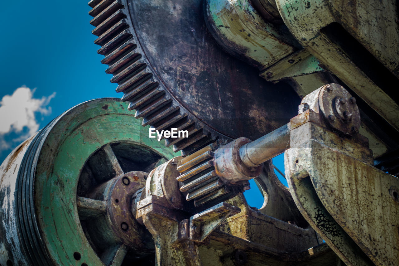 Low Angle View Of Rusty Machine Part Against Sky
