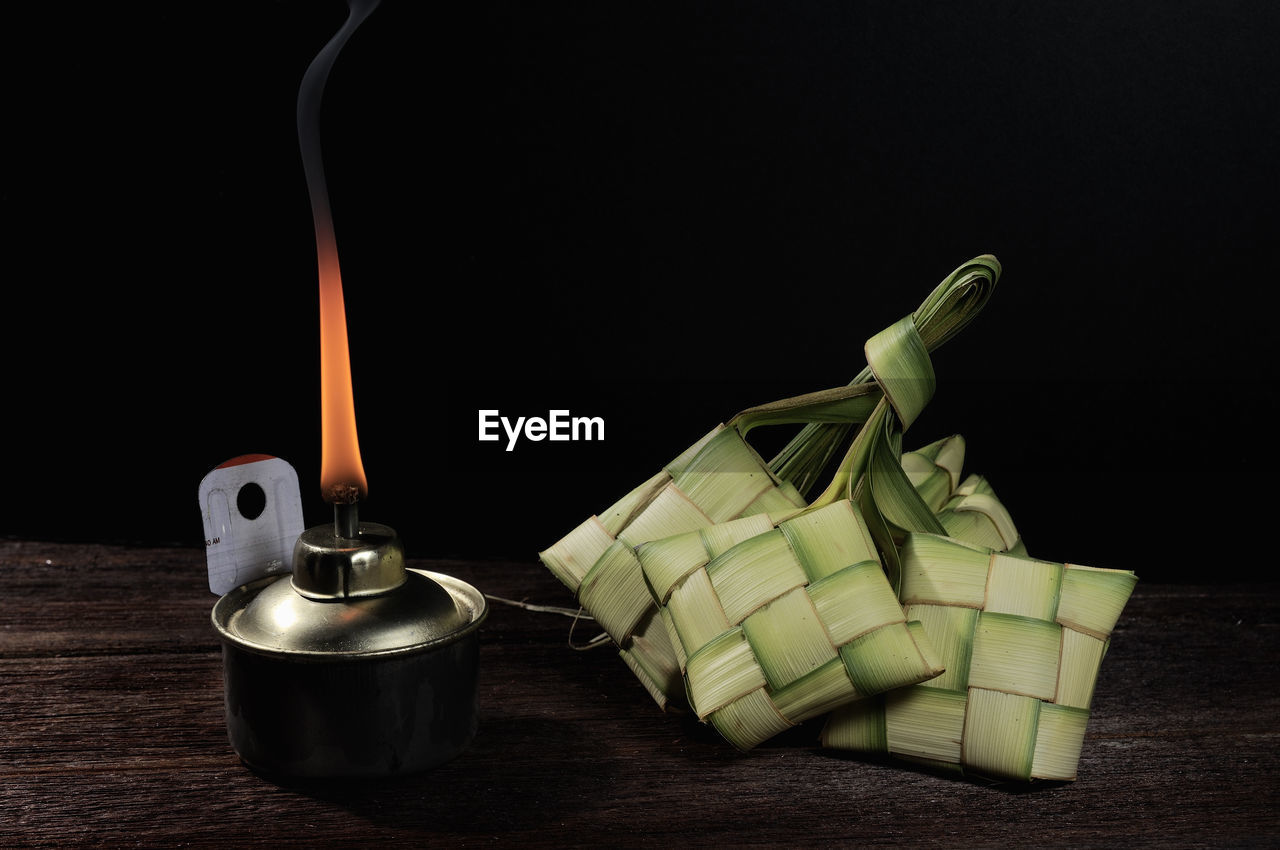 Close-up of oil lamp and ketupats against black background