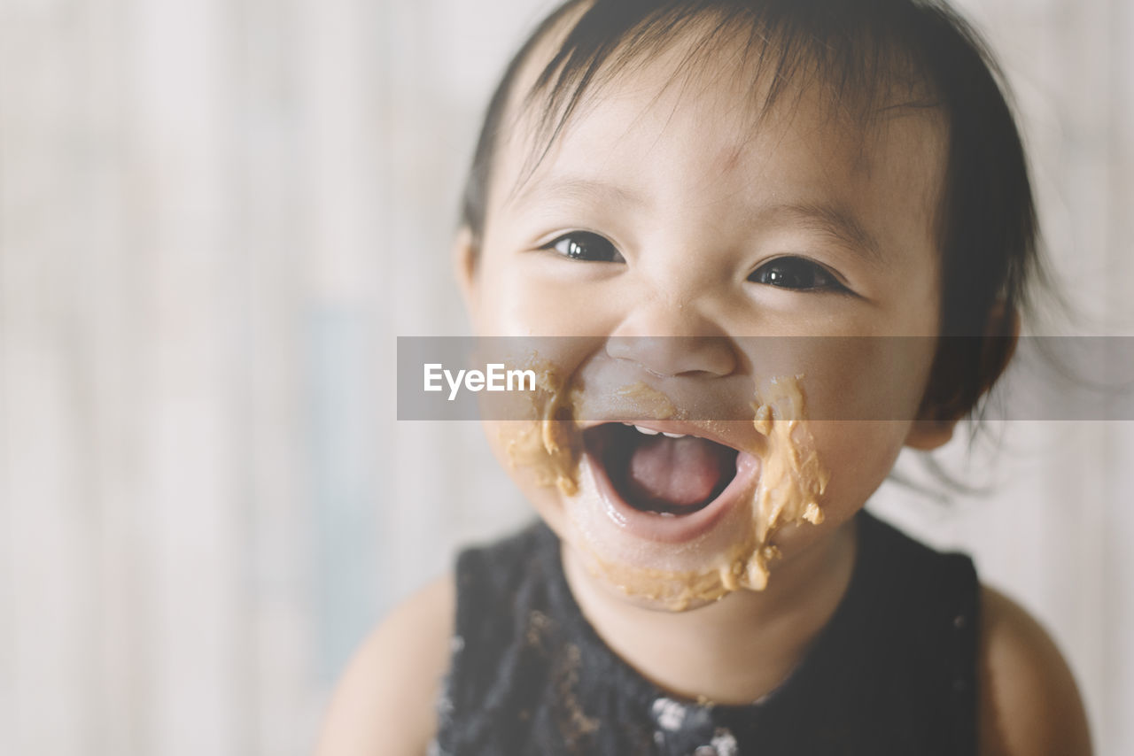 Close-Up Portrait Of Cute Girl With Peanut Butter On Face At Home
