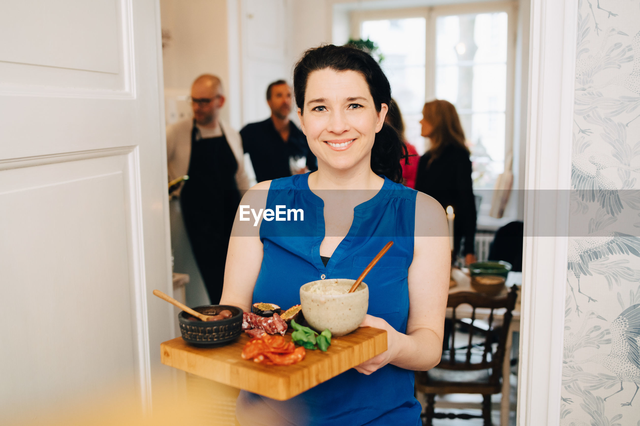 PORTRAIT OF SMILING YOUNG WOMAN STANDING BY FOOD AT HOME
