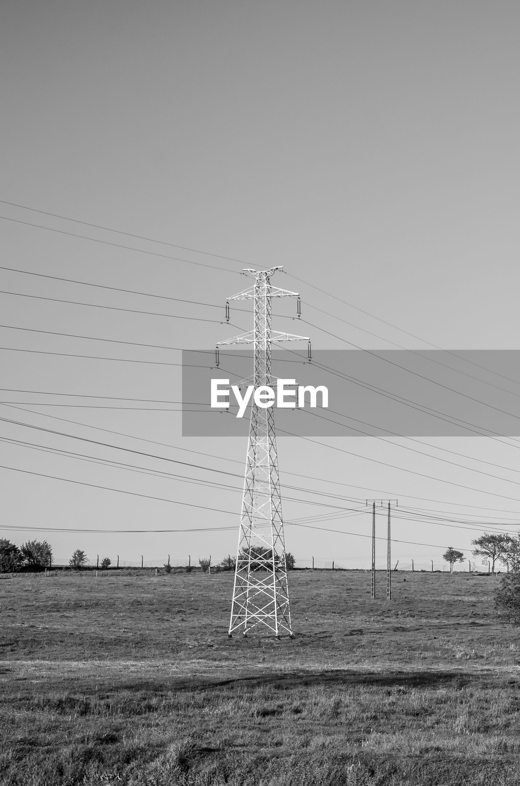 ELECTRICITY PYLONS ON FIELD AGAINST SKY