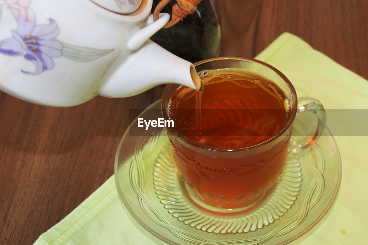 food and drink, drink, refreshment, table, pouring, cup, saucer, one person, indoors, mug, coffee, hot drink, crockery, freshness, close-up, coffee - drink, high angle view, real people, tea - hot drink, tea, hand, tea cup, temptation