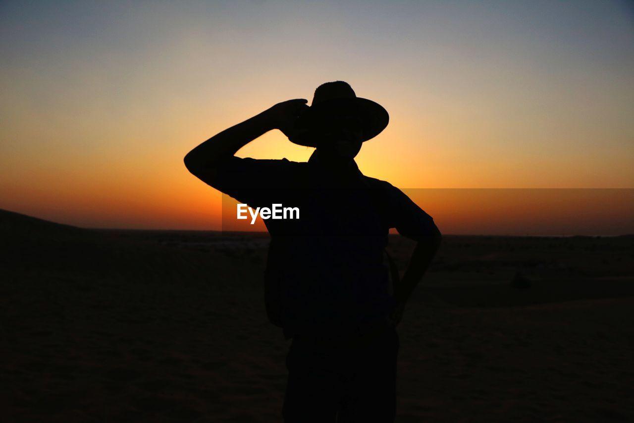 Silhouette Man Wearing Hat Standing Against Orange Sunset Sky
