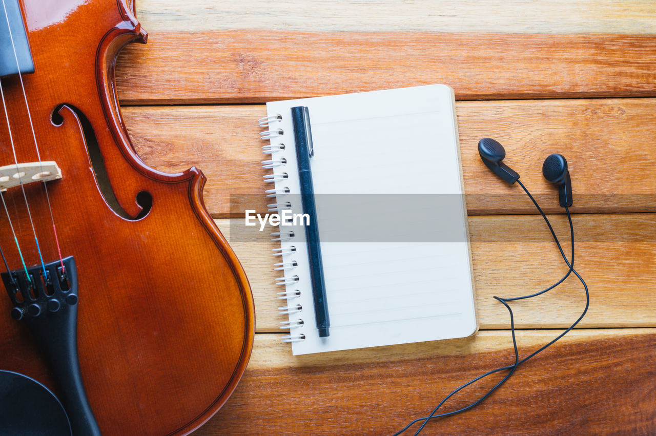 Directly Above View Of Diary And Violin On Wooden Table