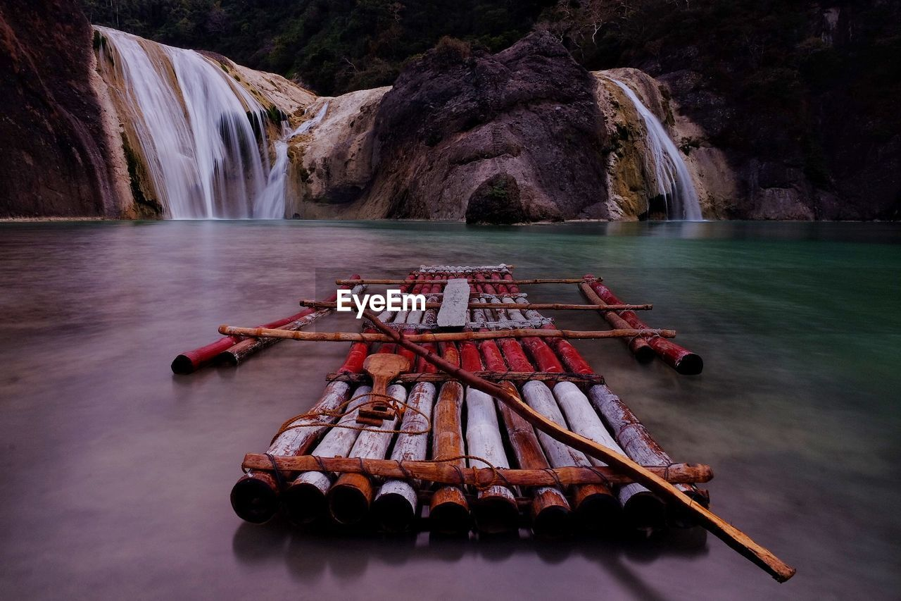 Wooden raft in river against waterfall