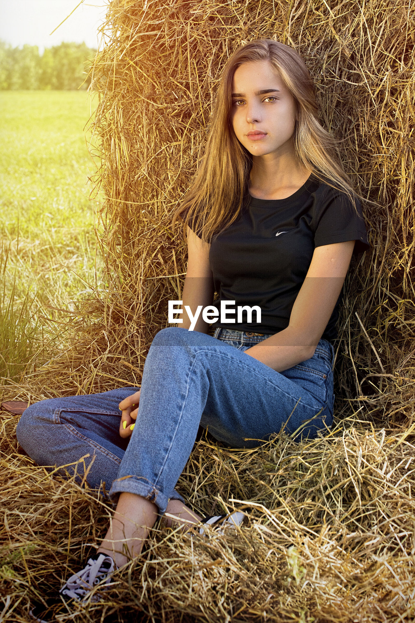 Portrait of young woman sitting against hay bale