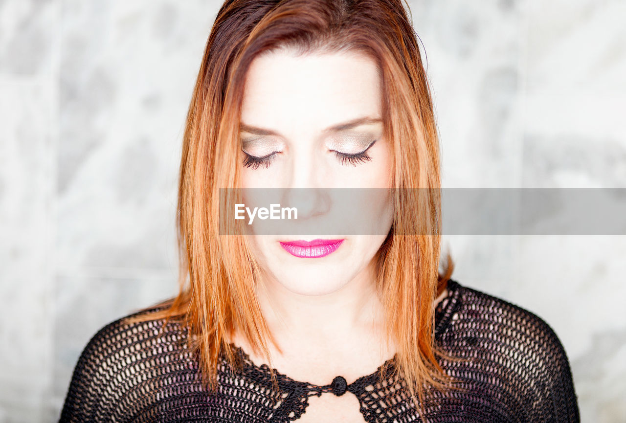 Close-up of woman with eyes closed wearing make-up