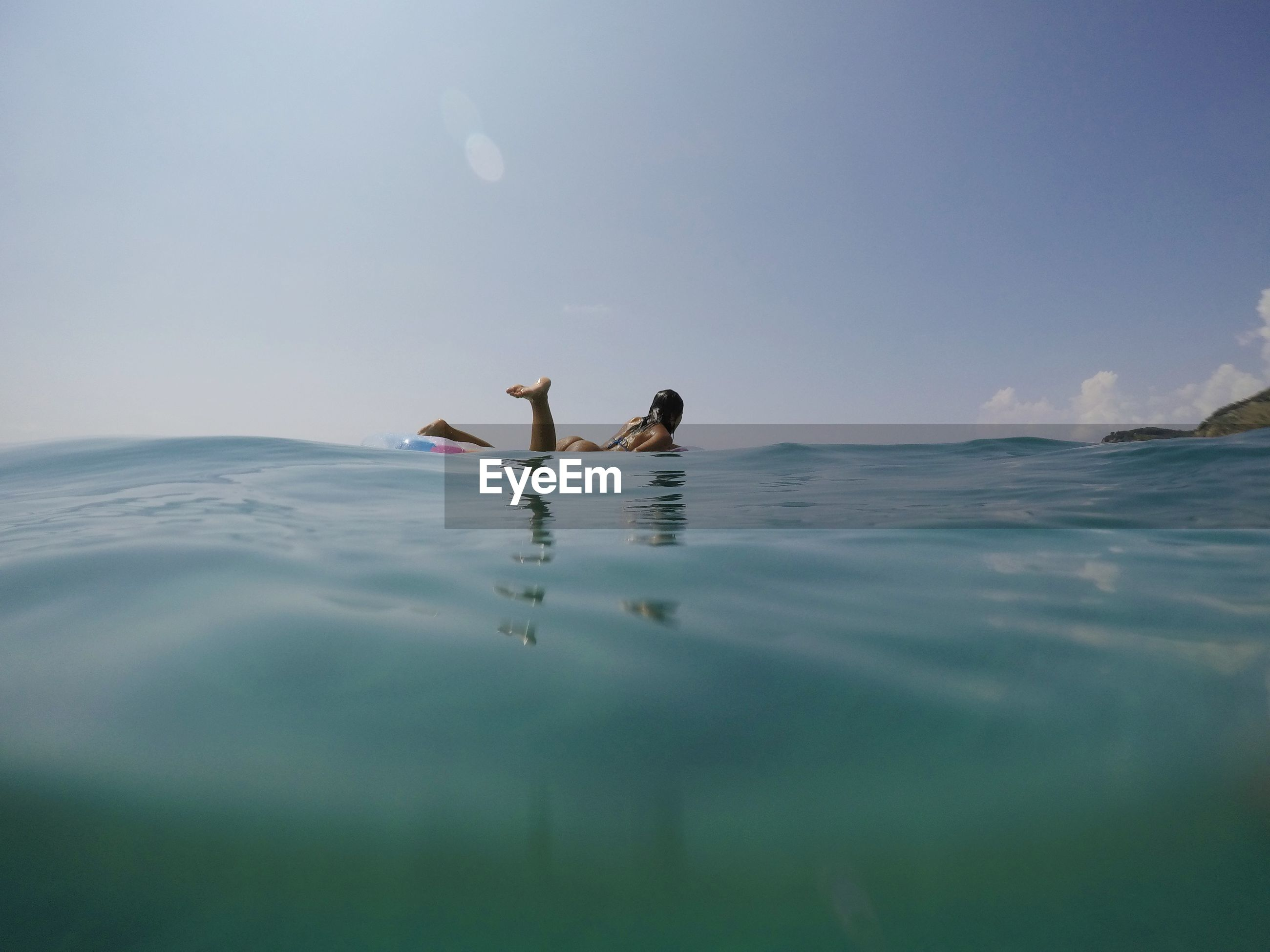 Full length of woman swimming in sea against sky
