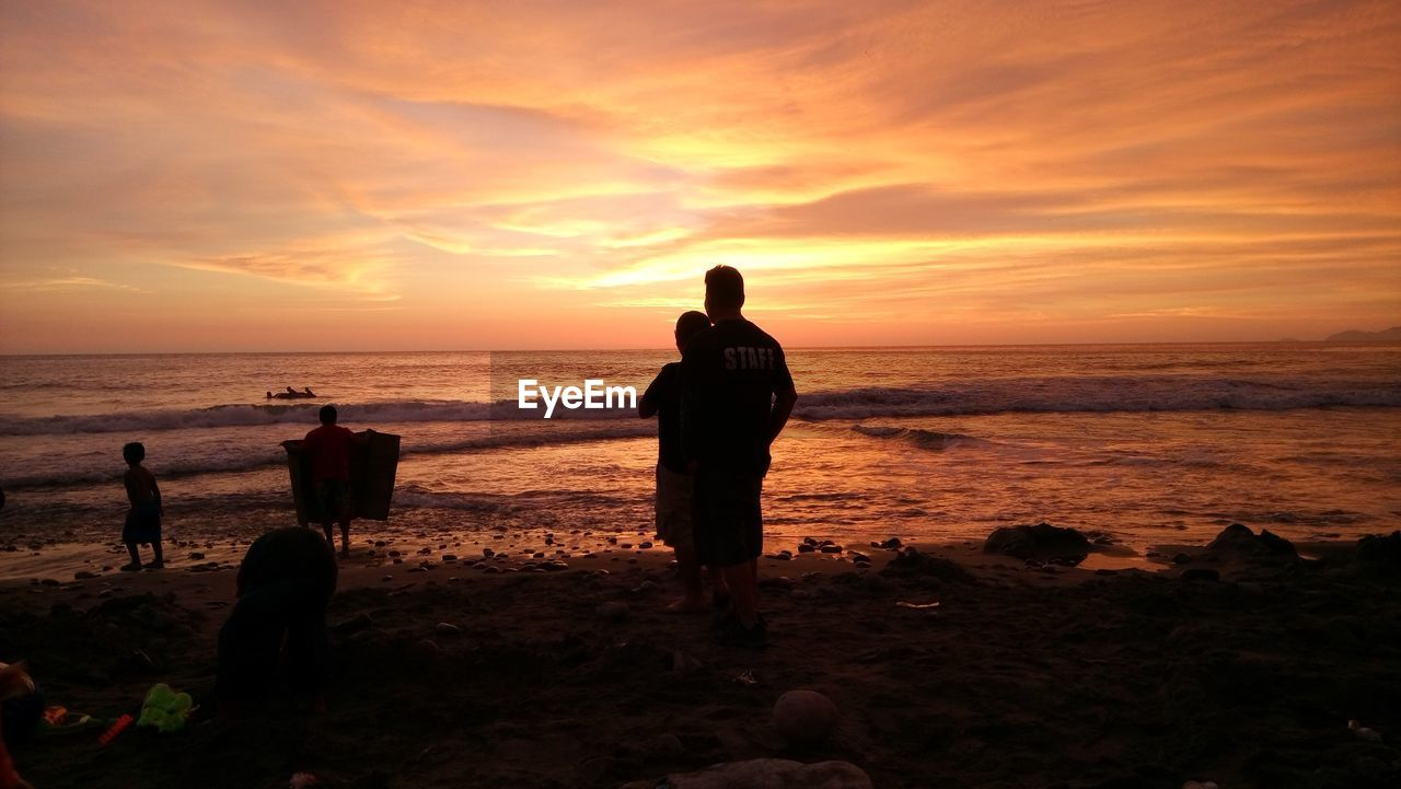 sunset, sea, beach, horizon over water, nature, scenics, beauty in nature, silhouette, orange color, sky, water, tranquil scene, togetherness, tranquility, real people, men, standing, full length, vacations, lifestyles, sand, outdoors, friendship, people