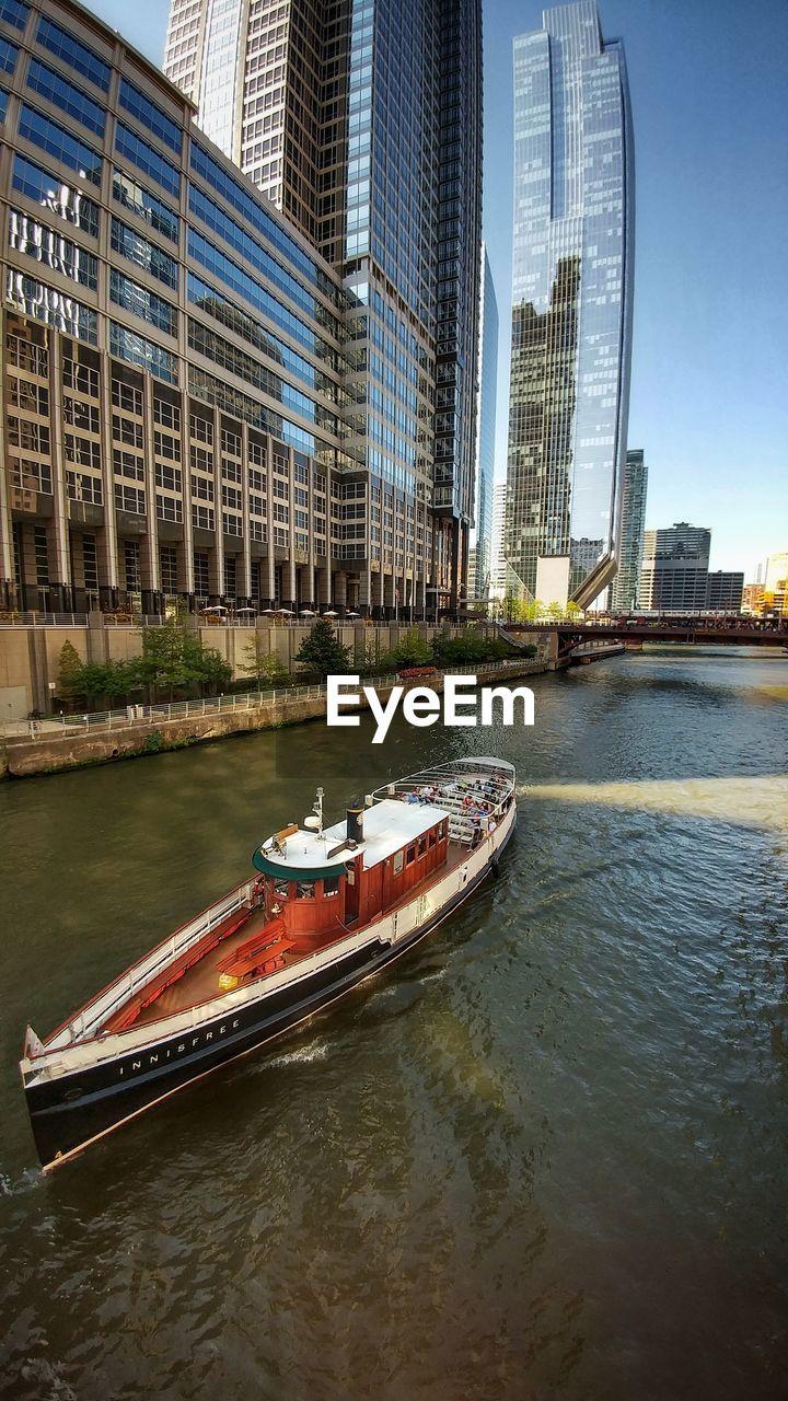 Modern Buildings By River In City Against Sky