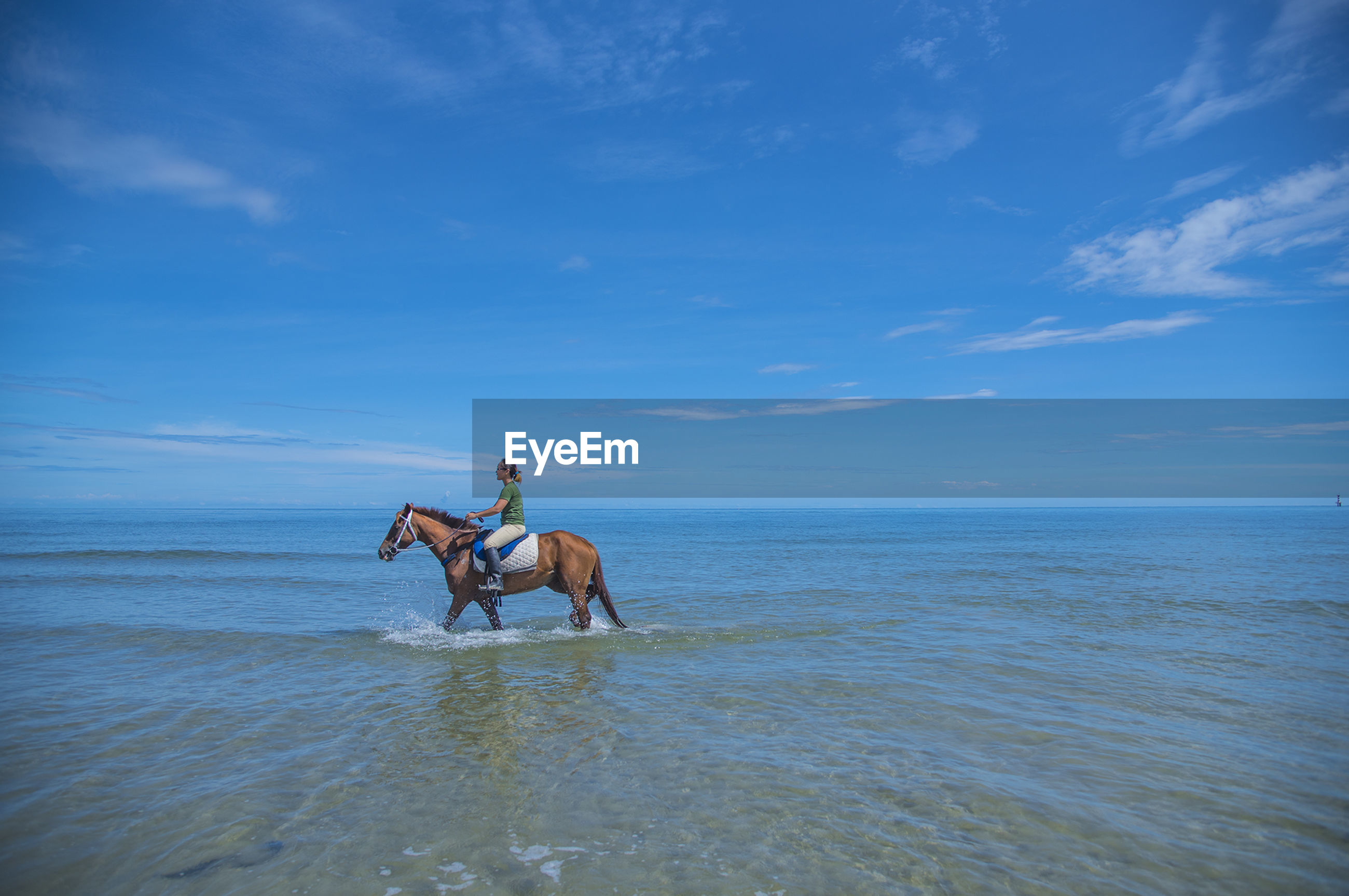 Full length of woman riding horse in sea against blue sky