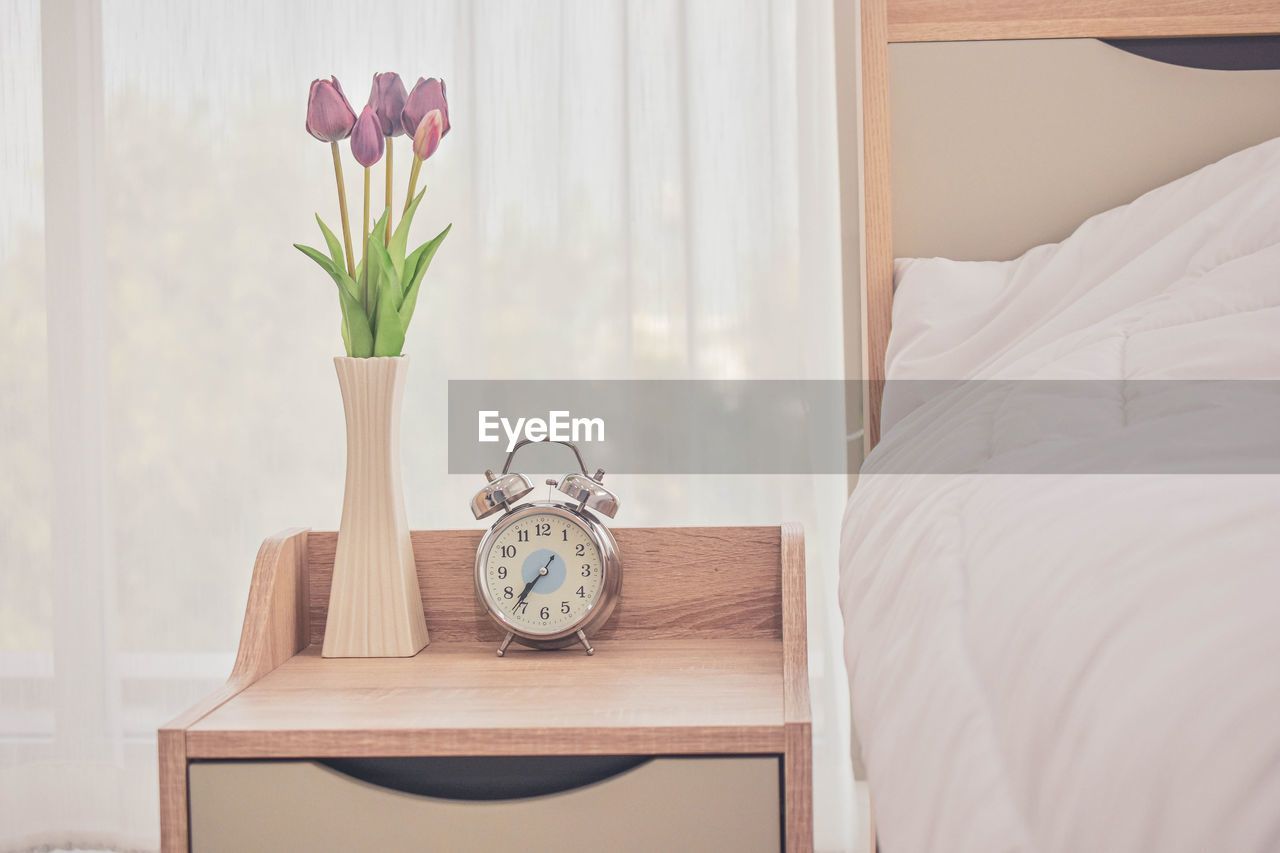 FLOWER VASE ON TABLE IN BED