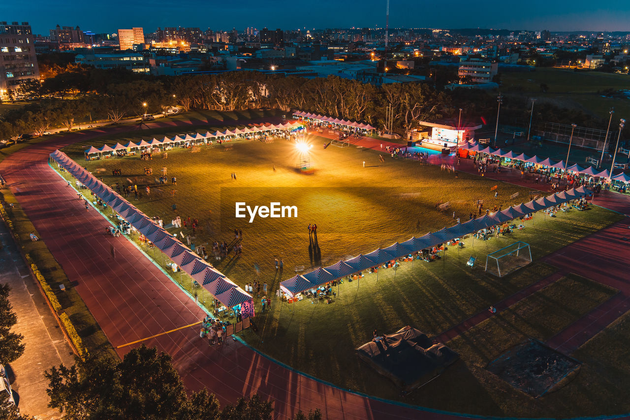 high angle view, illuminated, built structure, architecture, building exterior, outdoors, large group of people, night, real people, tree, water, city, sky, people
