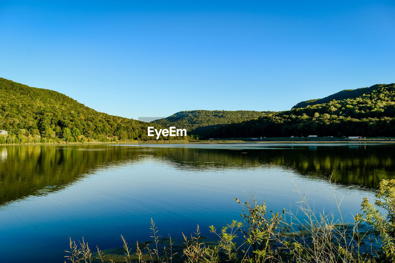 Scenic view of lake by tree mountains against clear blue sky