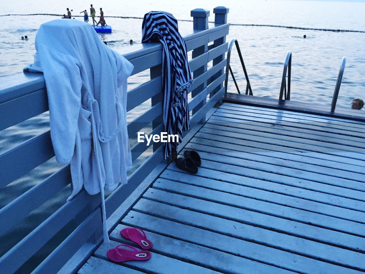 Flip-Flops And Bathrobes On Railing At Pier By Sea