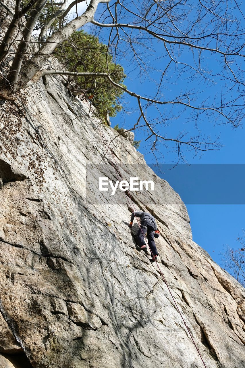 climbing, rock, low angle view, leisure activity, solid, real people, rock - object, adventure, nature, activity, rock formation, rock climbing, extreme sports, lifestyles, day, full length, sky, sport, people, men, outdoors, skill, formation, effort