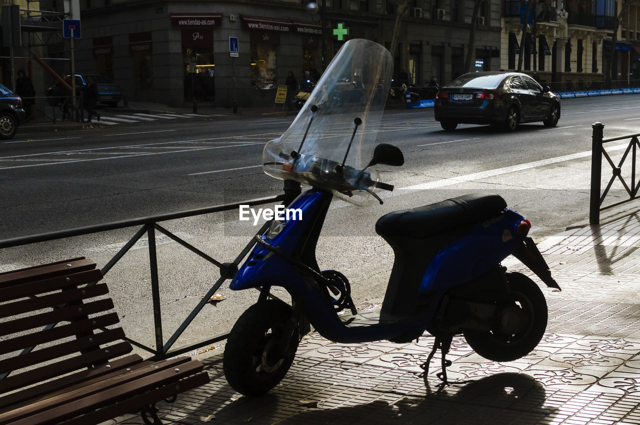 Motor Scooter Parked At Sidewalk In City