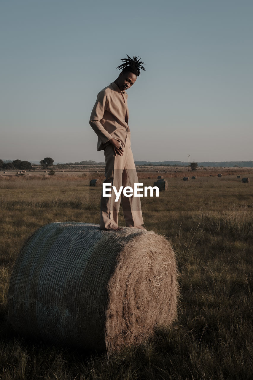 Full length portrait of young man standing on hay bale at agricultural landscape