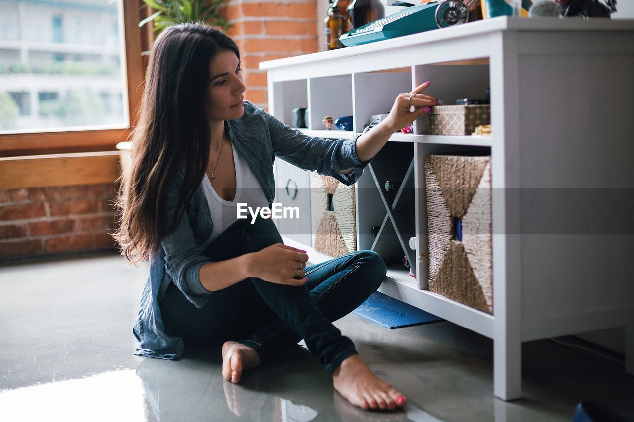 Woman Sitting By Shelf Indoors