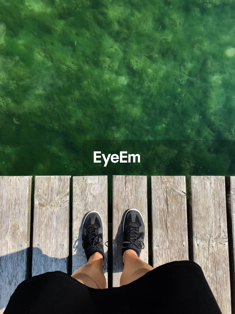 low section, human leg, body part, human body part, real people, one person, personal perspective, lifestyles, leisure activity, shoe, standing, unrecognizable person, day, wood - material, nature, women, water, human foot, outdoors, at the edge of, concrete, jeans