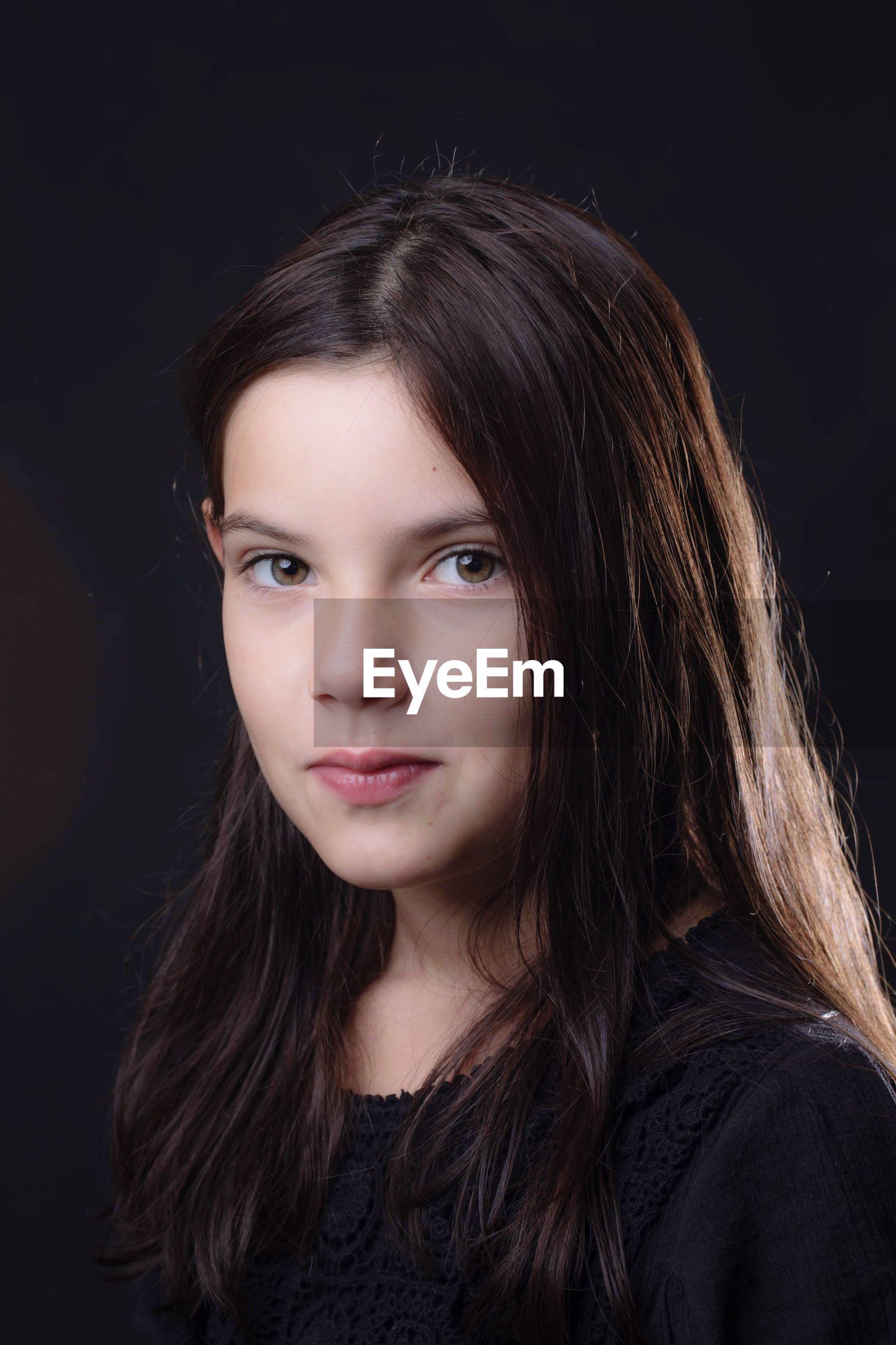 Portrait of girl against black background