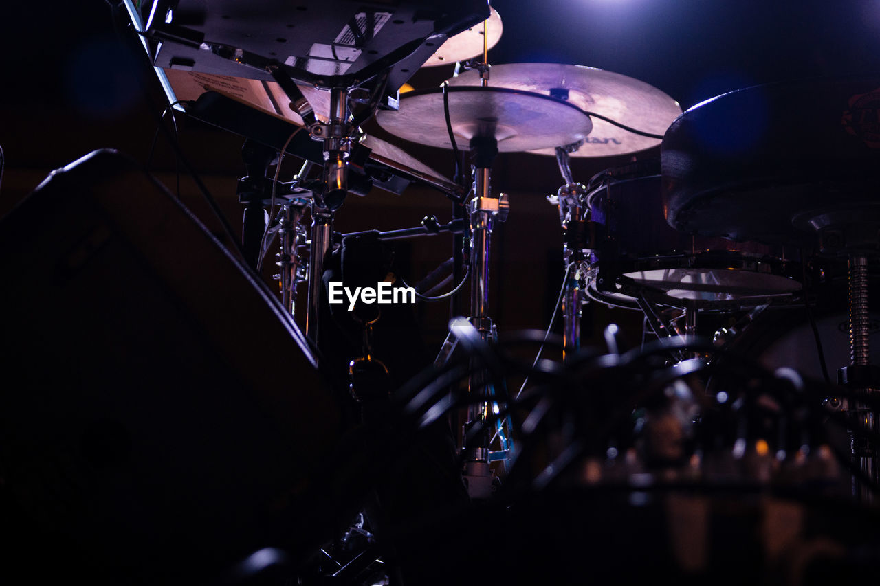 music, arts culture and entertainment, musical equipment, musical instrument, drum - percussion instrument, drum kit, nightlife, drum, percussion instrument, indoors, cymbal, stage, stage - performance space, close-up, illuminated, nightclub, performance, rock music, enjoyment, event, dark, concert, popular music concert, entertainment event