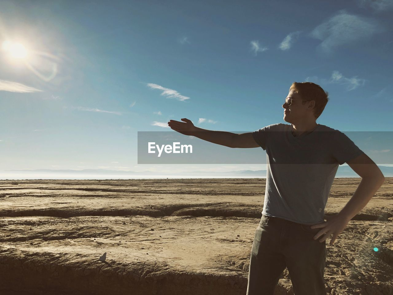 sky, one person, real people, land, lifestyles, sunlight, leisure activity, three quarter length, nature, standing, beach, beauty in nature, men, casual clothing, day, scenics - nature, water, front view, non-urban scene, outdoors, lens flare, human arm, bright