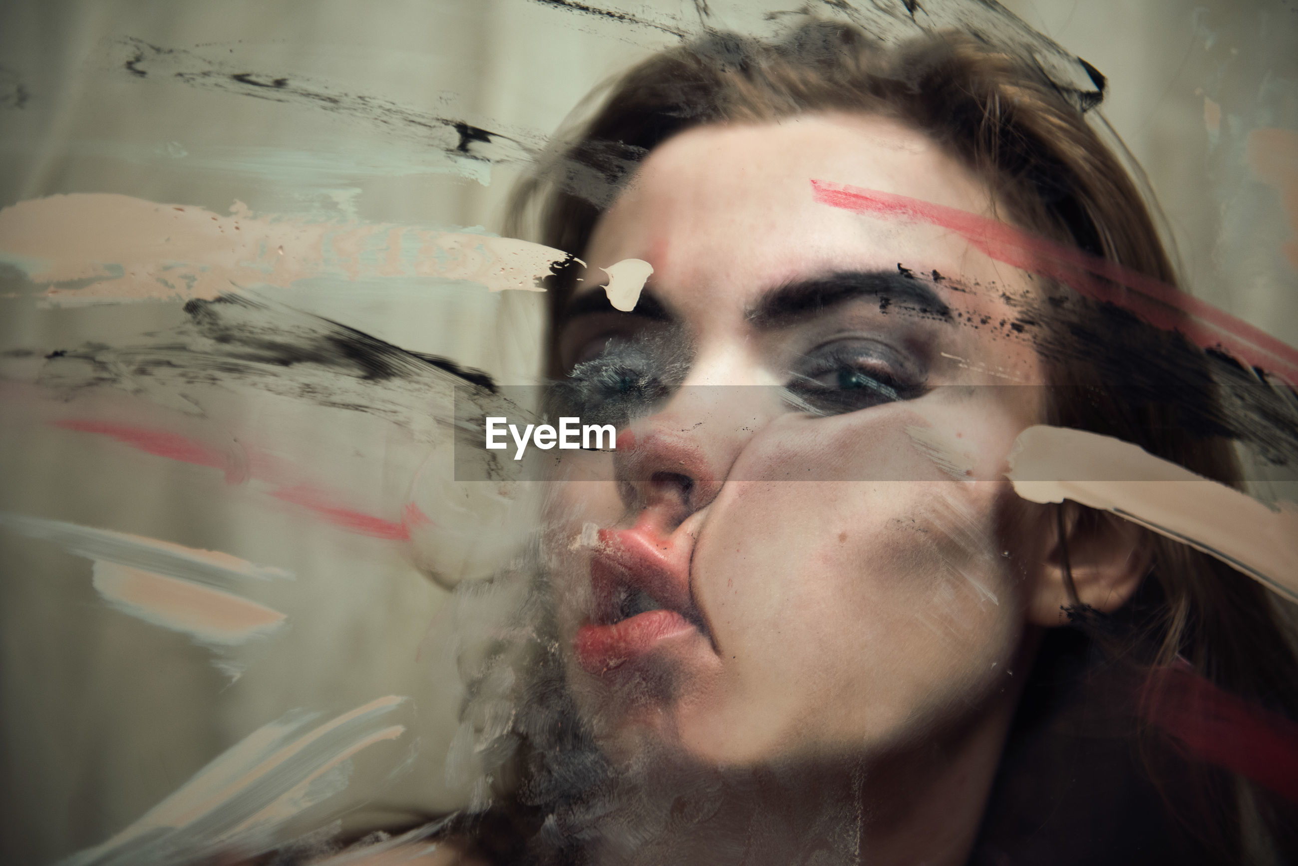 Close-up portrait of woman pressing her face on glass window