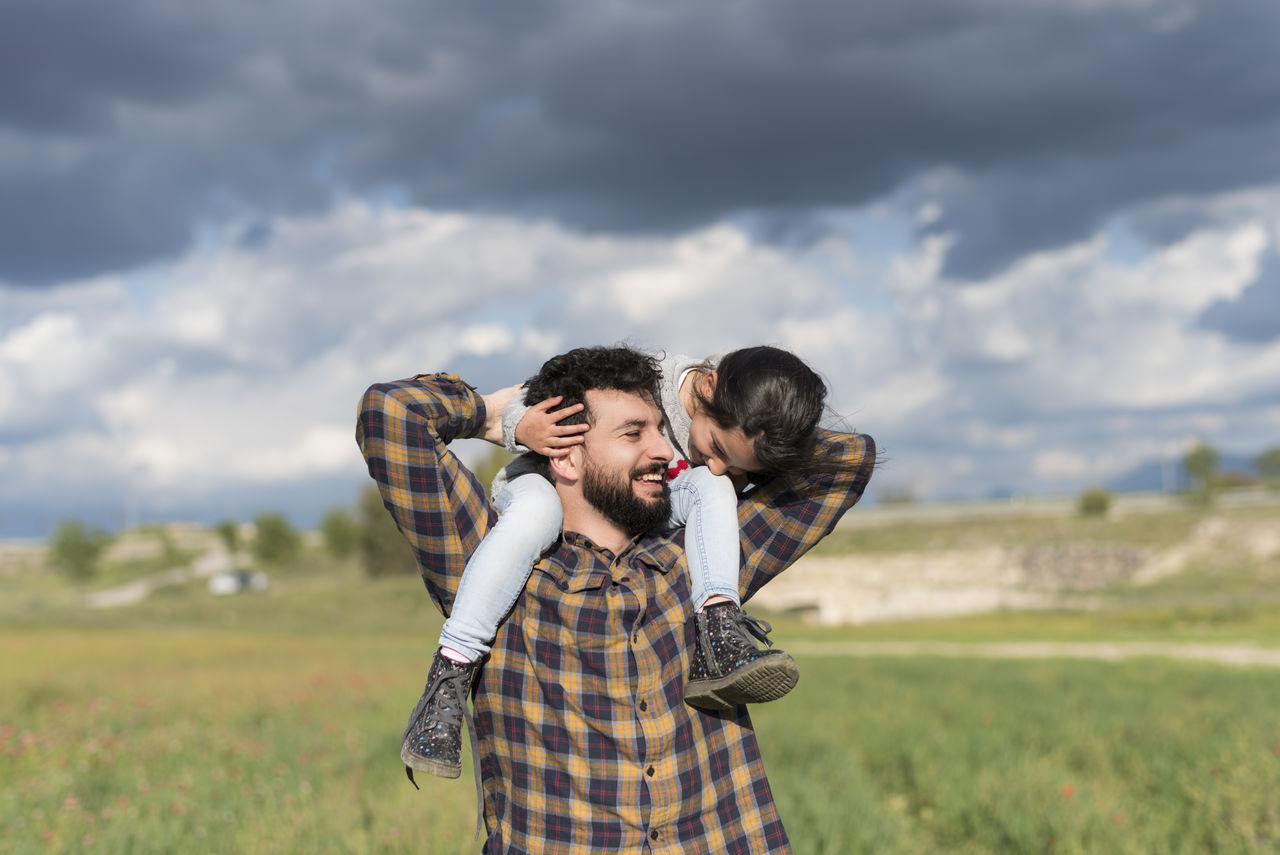 Smiling Man Carrying Daughter While Standing On Field Against Sky