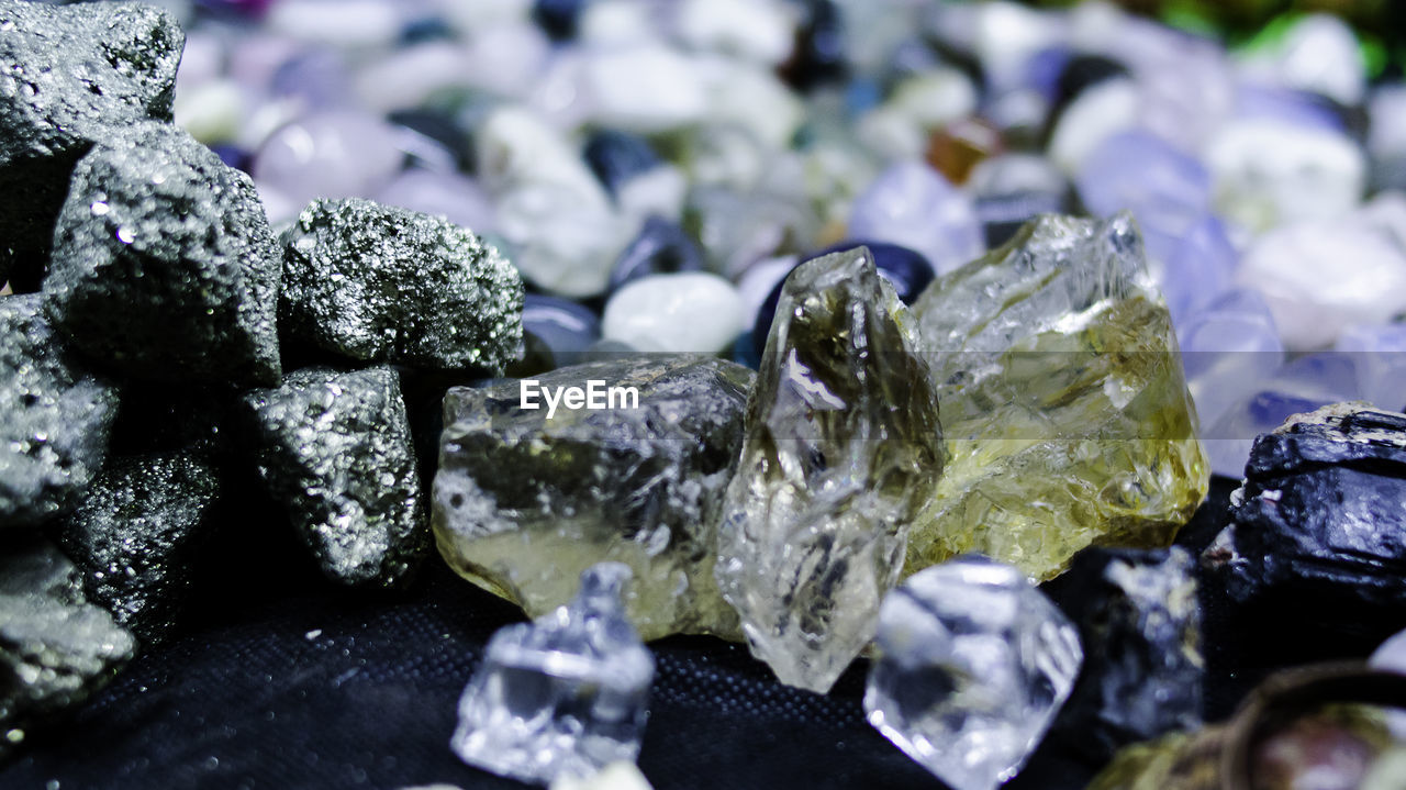 solid, no people, crystal, selective focus, close-up, rock, geology, mineral, rock - object, stone - object, jewelry, nature, still life, indoors, large group of objects, gemstone, focus on foreground, shiny, textured, precious gem, purity, pebble, quartz