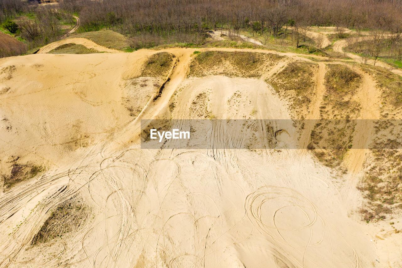 HIGH ANGLE VIEW OF SAND ON LAND