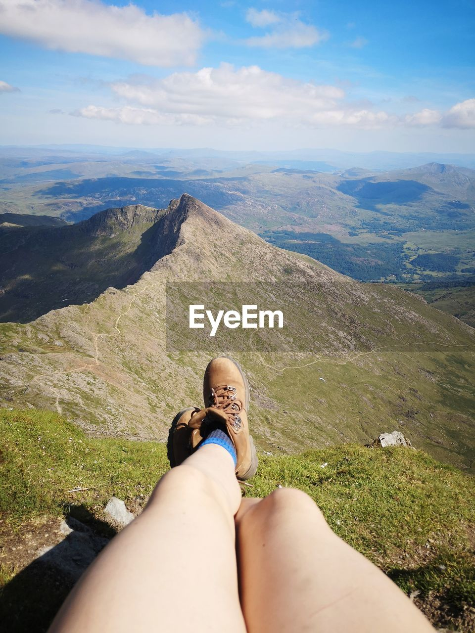 Low section of woman relaxing on mountain against sky