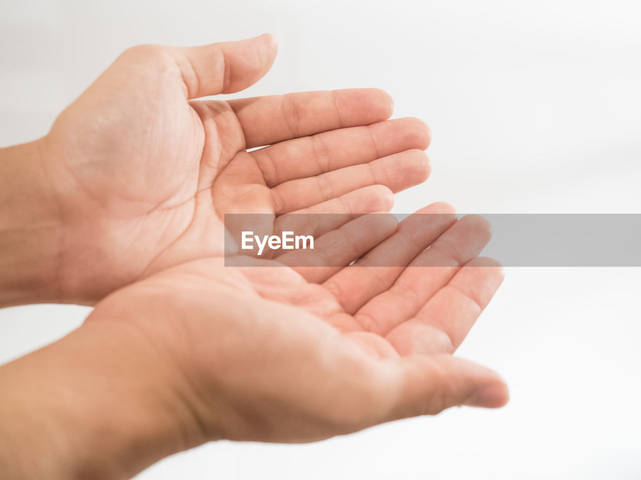 Close-up of hands cupped over white background