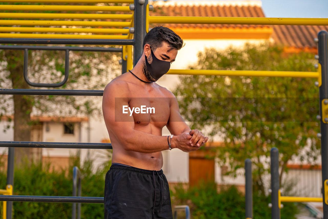 Full length of shirtless man standing against railing