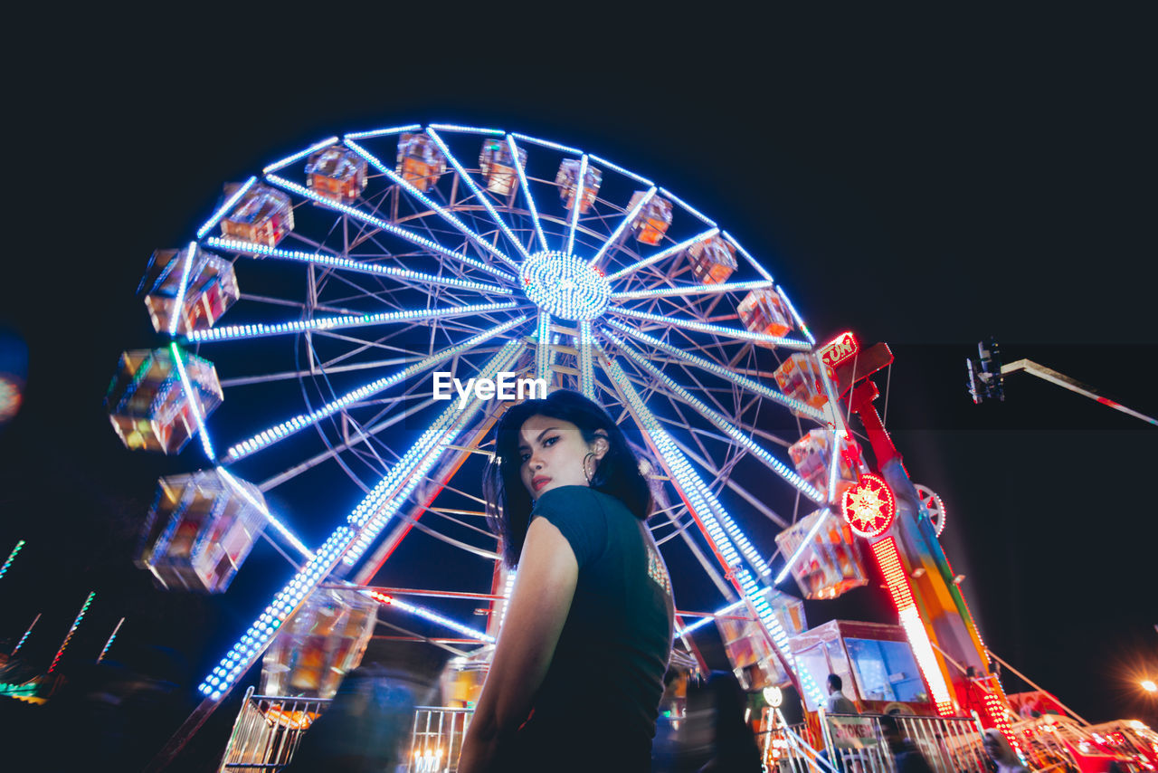 amusement park, amusement park ride, arts culture and entertainment, illuminated, night, leisure activity, ferris wheel, real people, lifestyles, low angle view, spinning, sky, motion, architecture, standing, one person, glowing, casual clothing, clear sky, outdoors