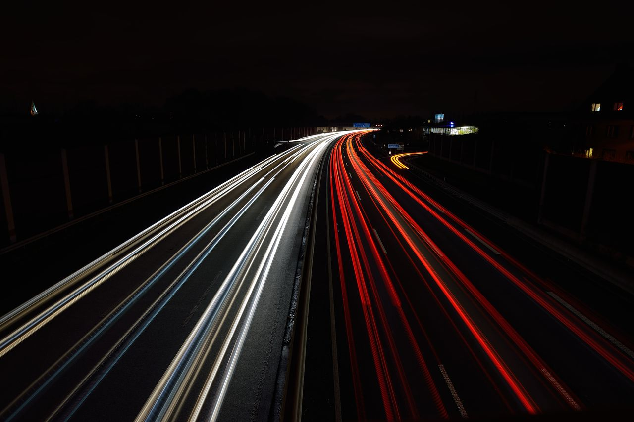 long exposure, light trail, illuminated, motion, speed, night, blurred motion, transportation, road, no people, architecture, highway, city, traffic, high angle view, red, tail light, street, city life, glowing, outdoors, multiple lane highway, vehicle light