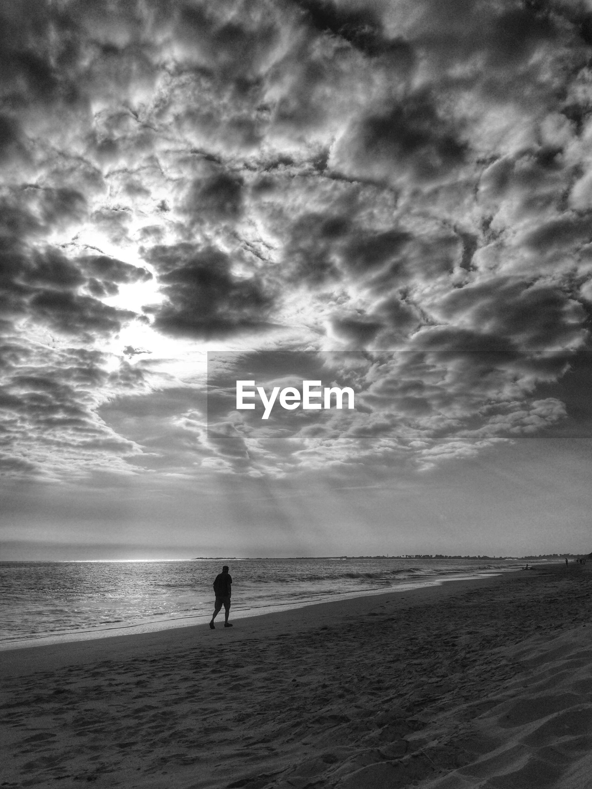 Scenic view of silhouette man walking on beach by sea against cloudy sky