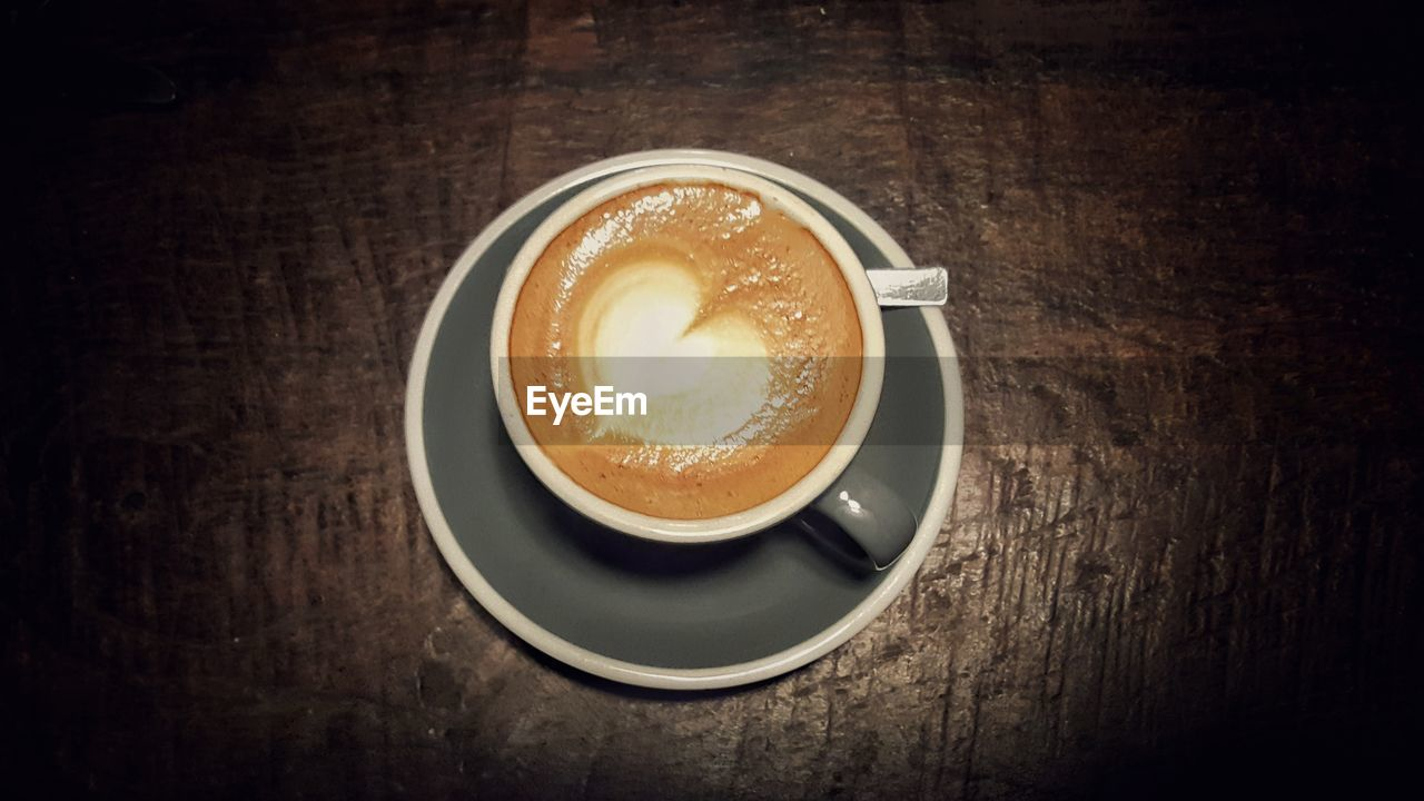 coffee - drink, drink, coffee cup, table, refreshment, food and drink, frothy drink, saucer, shape, high angle view, froth art, indoors, cappuccino, no people, freshness, close-up, latte, directly above, day