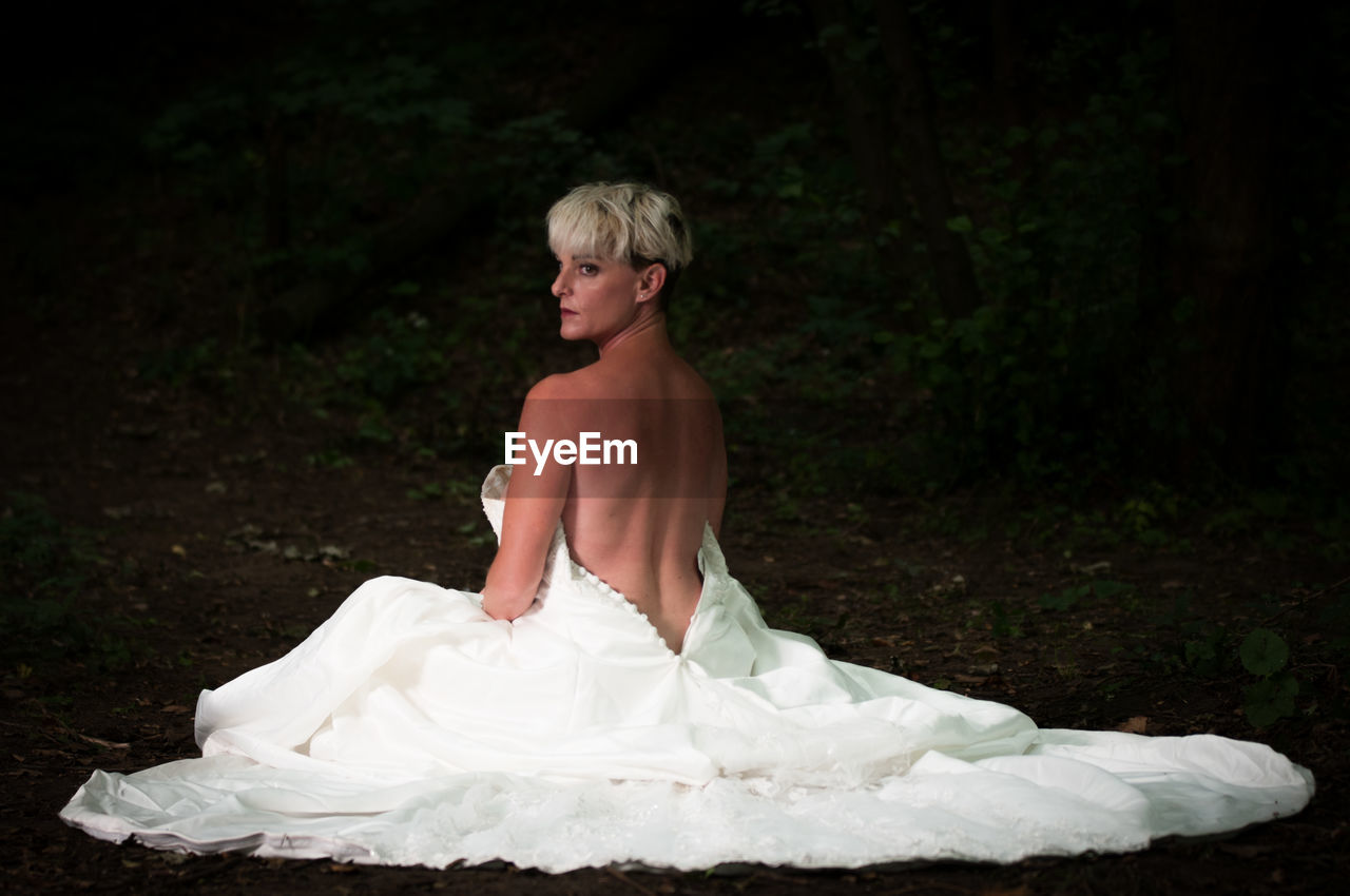 Bride wearing backless wedding dress sitting in forest