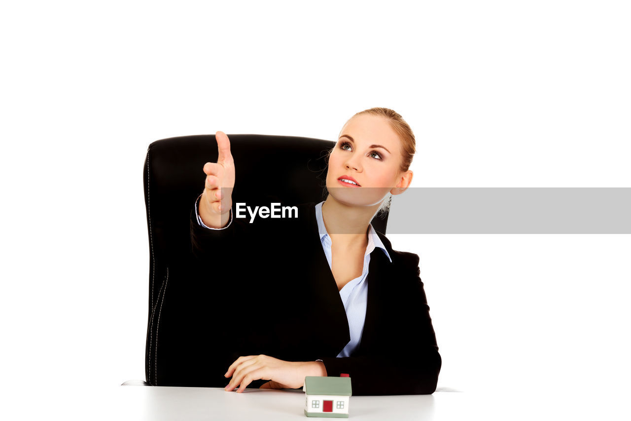 Businesswoman with model home greeting against white background