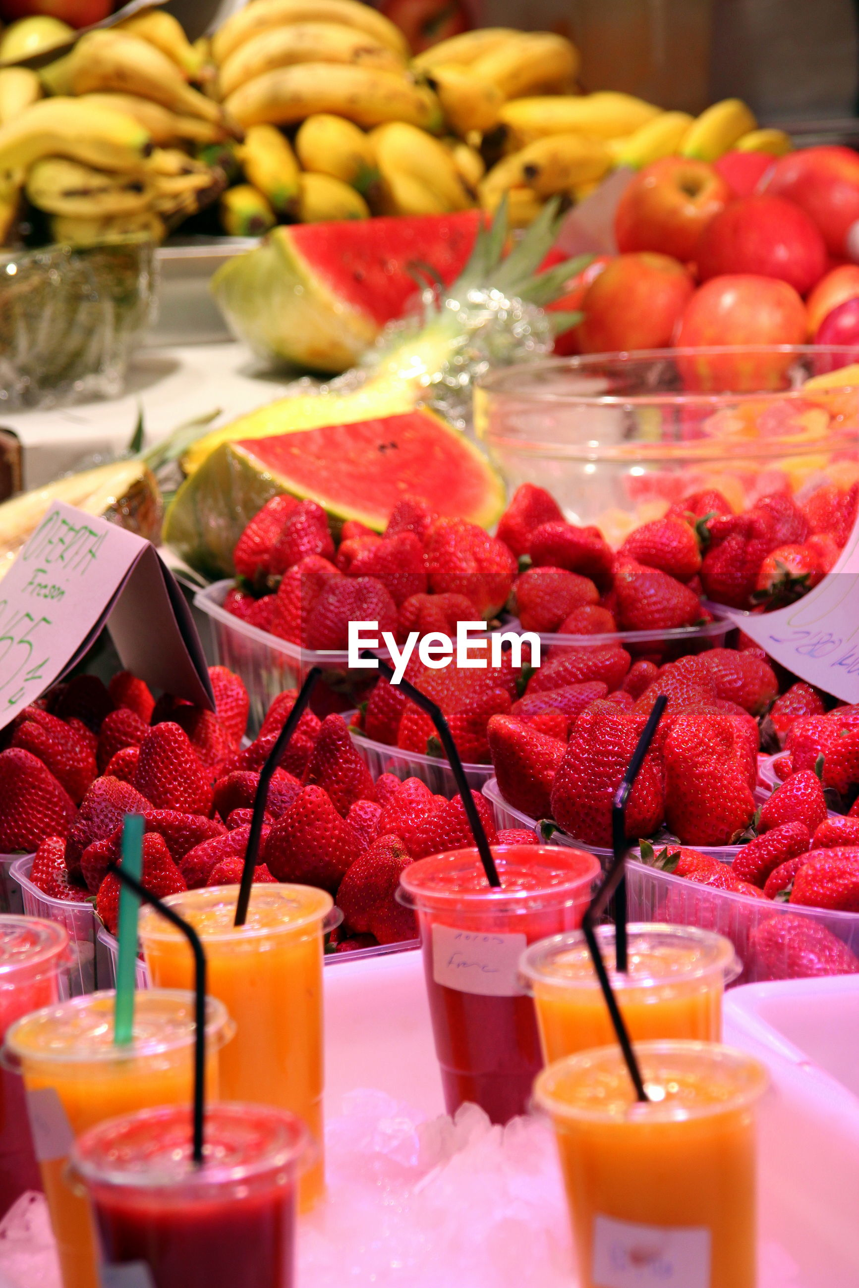 Fresh fruit and colorful juices, for sale on the market counter